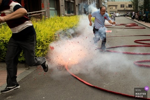 China wedding day photography | The groom took the bride home and set off firecrackers at the door of the house.