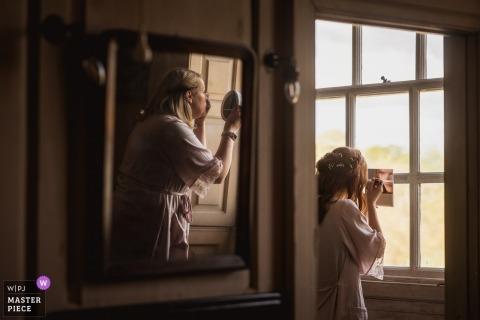 Fotografía de reportaje de bodas de Dorset Inglaterra en St Giles House, Wimborne | Espejo espejo, maquillaje junto a la ventana mientras se prepara