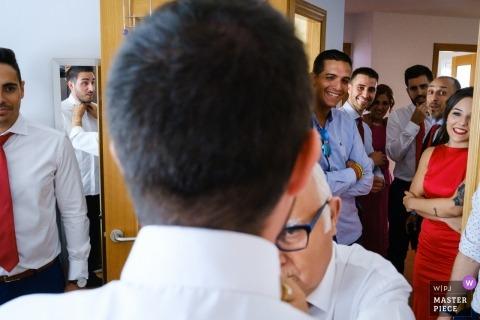 Pan młody otrzymuje pomoc w zakresie ostatecznych szczegółów, gdy przyjaciele i rodzina obserwują go w dniu ślubu Alcoy. - casa novio, fotografia alki