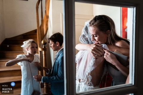 A friend kisses the bride with emotion through the window on wedding day in France. | Savoie wedding photography