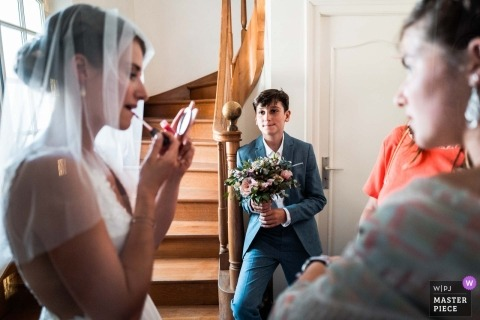 French bride geting ready for her ceremony as the little brother admires the bride's make-up with attention