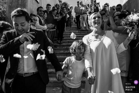 Bride, groom and their son with hit with confetti by the guests after their Château de Candie, Chambéry, France wedding ceremony.