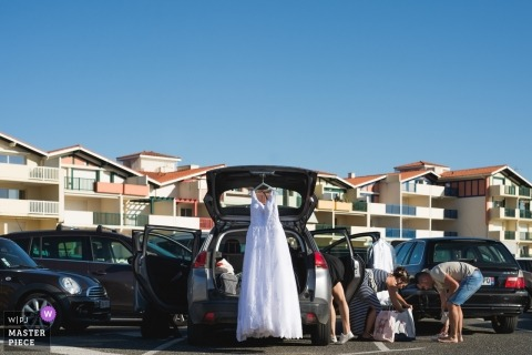 Vieux Boucaut, France wedding photo of the bridal party arriving in the parking lot, as weddng dress hangs from the backdoor hatchh of the car.
