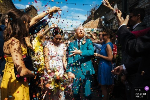 England wedding reportage photography - Bride and groom exit the ceremony as their guests congratulate them and the groom gets a mouthful of confetti