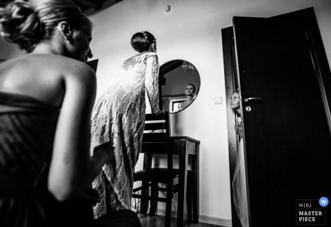 Pirin Golf Club, Razlog, Bulgaria | La novia que se mira en el espejo como una joven dama de honor entra en la habitación por curiosidad.