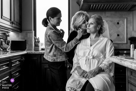 Rancho Santa Fe, California wedding photography of mom sneaking in a kiss while her daughter is having her makeup put on.