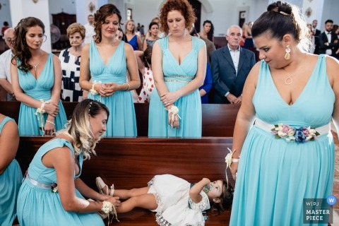 Bridesmaid ties flowergirl's shoes during a Iglesia de Las Rozas wedding ceremony.