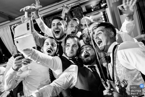 Mirador de Cuatro Vientos wedding photo of the groom and groomsmen taking a selfie (with a sword)