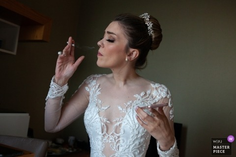 Istanbul, Turkey Wedding Photographer | Bride smoking a cigarette to relax with phone in her hand