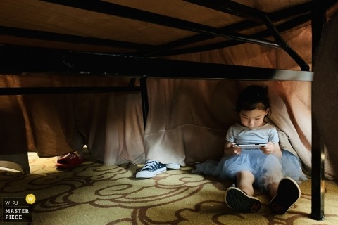 Fujian Hotel room wedding day photography | Children hide under the dining table and play with their mobile phones