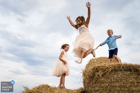 Photography at the venue location - the home of the wedding couple. Wedding bridal children enjoy bales of straw by jumping off tem.
