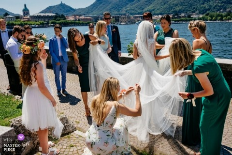 Netherlands outdoor wedding venue photo of bride with friends at the water fixing her dress