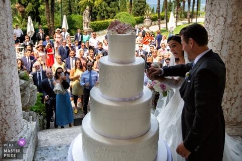 Huwelijksfotografie van buiten in Villa Cortine Palace Hotel - Sirmione - Gardameer - Italië - Afbeelding van grappig taartsnijden met de gasten op de achtergrond