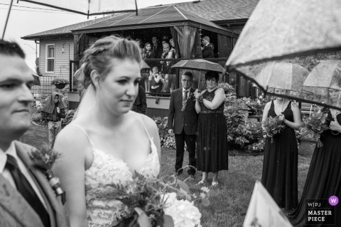Photography from Bride's Parents backyard, Daysland, AB, Canada - Wedding Ceremony image taken during the rain under umbrellas