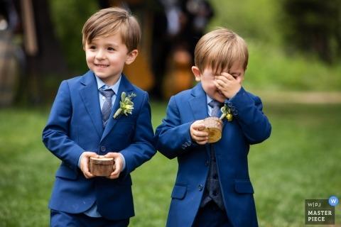 Lieu de la réception et du mariage Hideout, Kirkwood, Californie - Les photographes qui portent les alliances se marrent en se dirigeant dans l'allée au début de la cérémonie de mariage.