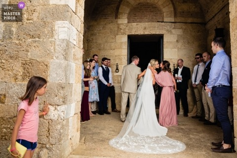 San Galgano, Tuscany, Italy Wedding Reportage Photographer - Image of a Tourist child peeping at bride outside church preparing to walk in, bridesmaid air kiss.
