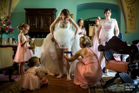 Wedding Photography from the Chateau Valeč - Installing the garter for the bride while getting ready.