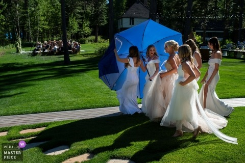 West Shore Lake Tahoe, CA Wedding Photography - Image of Bridesmaids hide the bride behind an umbrella on the way to her ceremony.