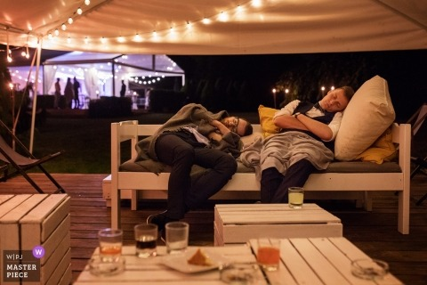 Cracow wedding photography of sleeping men at the reception party with tents