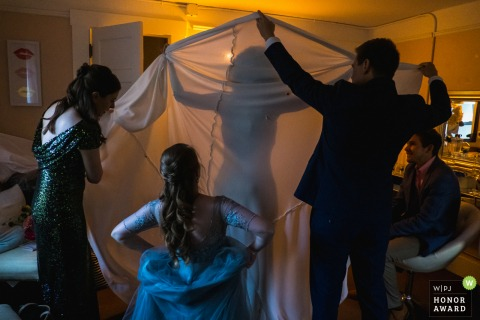 The bride gets help from her groom and friends to bustle the train of her wedding dress. | Photo from venue: Deer Park Villa, Fairfax, California