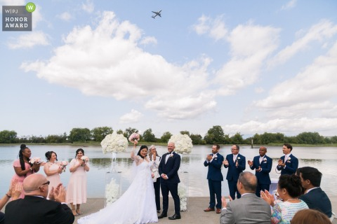 UBC Boathouse, Richmond, BC outdoor wedding venue photo | An airplane flies by as the newlyweds celebrate.
