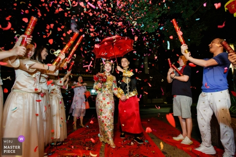 Dongguan, China actual day wedding photography of the bride and groom - back to home under red umbrella and confetti cannons