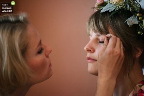 Photo at an Air bnb the morning of the wedding, rented by bride and bridesmaids | friends apply makeup on each other