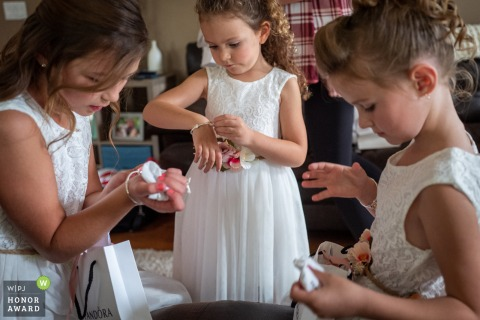 Bride and Groom's house, Edmonton, AB, Canada | Wedding photo of the flower girls opening their gifts from the bride