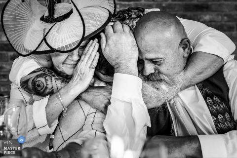Pryors Hayes Trouwfotografie in zwart en wit - Bruidegom knuffelt zijn moeder en vader