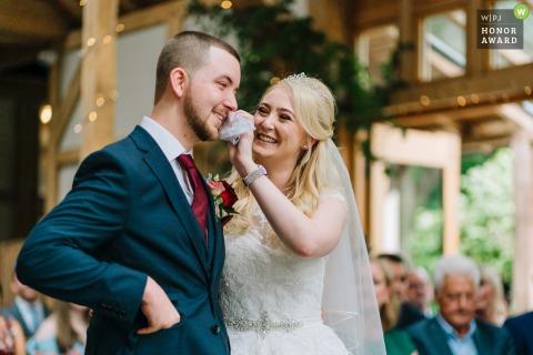 Foto di Oak Tree Of Peeover durante la cerimonia al coperto | Lo sposo piange e si fa asciugare la lacrima dalla sposa