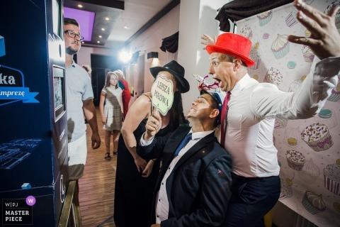 Fotografia miejsca w domu weselnym Venge, Łódź, Polska - Grupa gości weselnych wygłupia się przed budką fotograficzną.