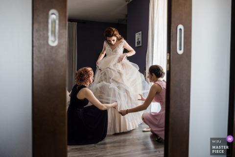 Photo de mariage en Bulgarie de la mariée recevant de l'aide pour s'habiller avant la cérémonie
