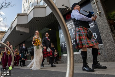 Alberta wedding photography Near ceremony | Wedding party recessional with bagpiper (from ceremony to the pub)
