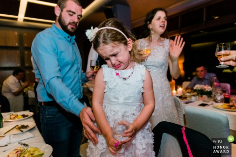 Sofia wedding photographer in Bulgaria | Little guest of the wedding crying, while her parents greeting the newly weds.