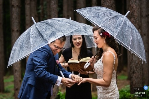 Rainy Day Wedding Photos from Roxbury Barn, Roxbury NY | Groom struggles to put ring on bride's hand in the rain