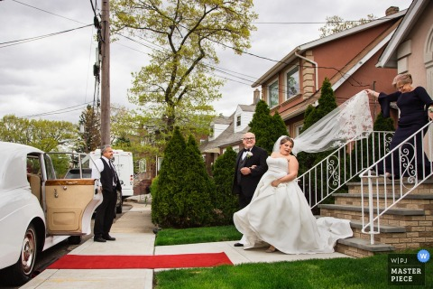 Wedding Photography from New Jersey | Bride being escorted to a car before ceremony, mom holds veil behind bride too tightly, bride gives a look