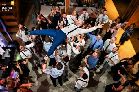 New Jersey Wedding Photographer | Groom is lifted into the air during reception and he decides to drink his beer