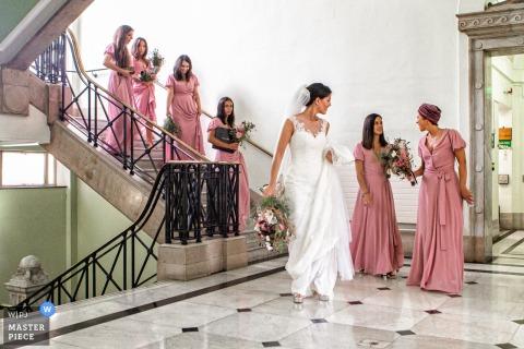 Ayuntamiento de Islington, Londres Fotografía de la boda de la novia y las damas de honor que bajan las escaleras en sus vestidos con flores