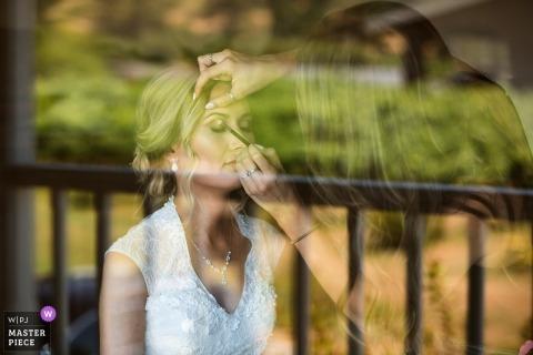 Huwelijksfotografie van Lula Cellars, Anderson Valley, CA | Weerspiegeling van wijngaarden in een venster met de bruid die haar make-up gedaan krijgt