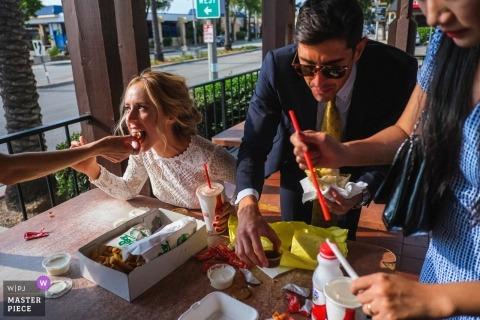 Huwelijksfoto's van na de ceremonie in Pasadena, CA, St. Andrew Catholic Church | De bruid en bruidegom eten fastfood met hun vrienden en familie na hun kerkelijke ceremonie
