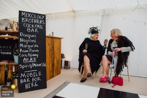 Private farm near Ely, UK - Wedding reception photography of two older women having a drink near the bar