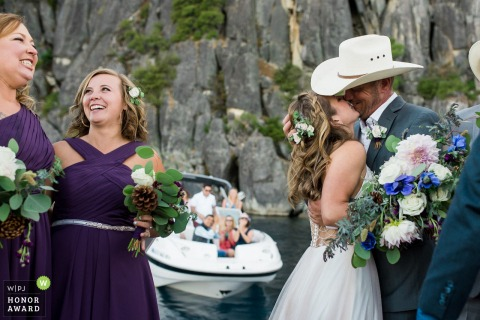 California outdoor wedding photography | Bride and groom seal their vows with a kiss at a Floatilla Boat Wedding in South Lake Tahoe, CA