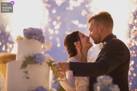 Villa Castellani foto de la boda de la novia y el novio cortando el pastel con fuegos artificiales en el fondo.