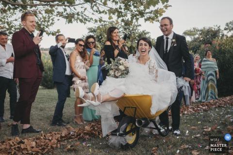 San Girio alla Fonte wedding image of the bride taking a ride in a wheelbarrow after the ceremony.
