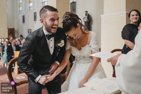 Fotografía de la boda de Chiesa Sant'Anna de la novia y el novio riéndose al darse cuenta de que el anillo estaba siendo puesto en la mano equivocada.
