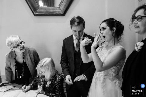 De huwelijksfotografie van Canada in zwart-wit van de bruid die met haar ring pronkt als de getuigen ondertekenen.