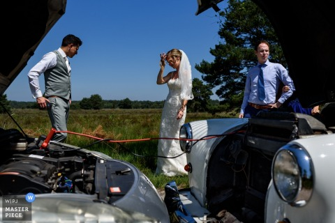 NL Wedding Photojournalism - The car battery of the Wedding Vehicle went down. It is being recharged while the groom just had a phone call with the ceremony venue. The bride stands with her hand in her hair.