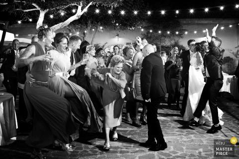 Photographe de mariage en Sicile prend une photo d'amis de tous âges alors qu'ils dansent joyeusement au mariage au Baglio Oneto à Marsala