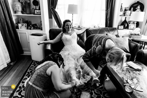 New York bride gets help with her shoes while she relaxes in her livingroom prior to the wedding ceremony.