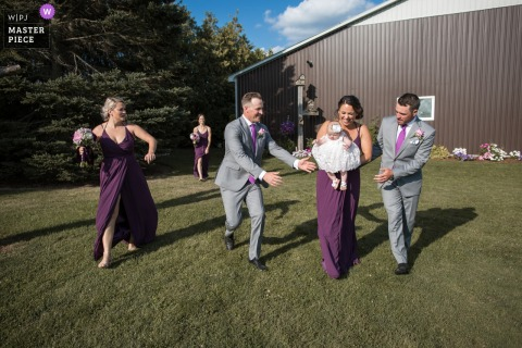 "London, Ontario wedding photographer: ""Just after the ceremony, the wedding party was dashing away when the bridemaid holding the flower girl almost trips. The groomsmen were on cue reaching for the baby."""